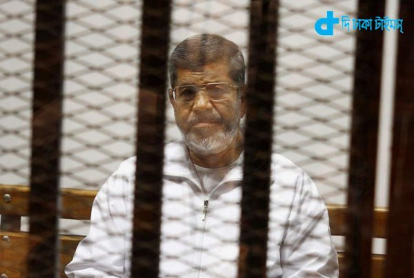 FILE - In this file photo taken Thursday, May 8, 2014, Egypt's ousted Islamist President Mohammed Morsi sits in a defendant cage in the Police Academy courthouse in Cairo, Egypt. Besides the current charges against him of conspiring with foreign groups, inciting the murder of his opponents and orchestrating prison breaks during the 2011 uprising that toppled his predecessor, Hosni Mubarak, Egypt's state prosecutor is now investigating allegations that Morsi leaked secret documents to Qatar via the Doha-based Al-Jazeera broadcaster, judicial officials said Wednesday, Aug. 27. (AP Photo/Tarek el-Gabbas, File)