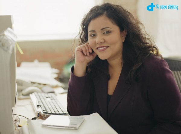ca. 2002 --- Businesswoman Sitting at Desk --- Image by © Royalty-Free/Corbis