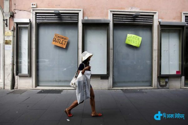 A pedestrian carries a plastic shopping bag as she passes a closed-down temporary outlet store in Rome, Italy, on Tuesday, Aug. 12, 2014. Italy's economy shrank 0.2 percent in the second quarter after contracting 0.1 percent in the previous three months. Photographer: Alessia Pierdomenico/Bloomberg via Getty Images
