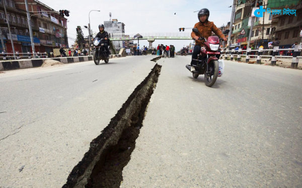 epaselect epa04721416 Motorcyclists use both sides of a wide crack in the Koteshwor-Suryabinayak Highway caused by the earthquake in the Bhaktapur area near Kathmandu, Nepal on 26 April, 2015 -- twenty four hours after a devastating quake which so far has taken the lives of at least 2,400. EPA/Hemanta Shrestha